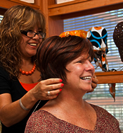 Cosmetologist Anabella Guillen helps a customer choose a wig.