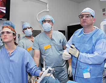 Dr. Raphael Bueno (right) views a video-scope during thoracic surgery.