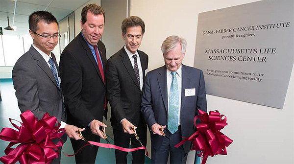(From left to right) Huy Nguyen, MD, interim executive director and medical director of the Boston Public Health Commission, Angus McQuilken, MLSC vice president for communications and marketing, Barrett Rollins, MD, chief scientific officer at Dana-Farber and Edward J. Benz Jr., MD, Dana-Farber president and CEO, participate in a ribbon-cutting ceremony to celebrate the official opening of Dana-Farber's Molecular Cancer Imaging Facility in Boston's Innovation District. (Photo credit: Michael Blanchard)
