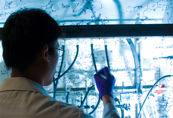 a researcher writing on glass in his lab