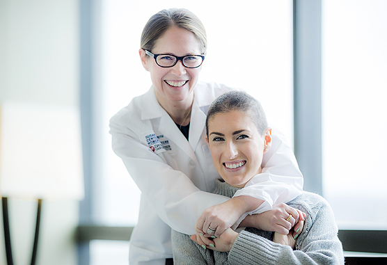 Lauren Czapla, NP, warmly embraces young adult patient Alexis Flanagan