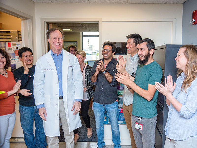 William Kaelin Jr., MD, being greeted by some members of his lab