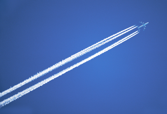 Airplane in sky with contrails