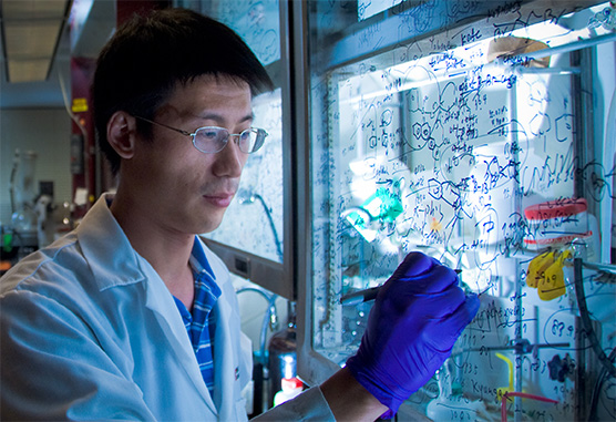 researcher writing on glass in lab