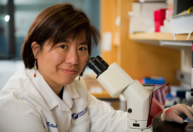 Catherine Wu, MD, sitting at a microscope