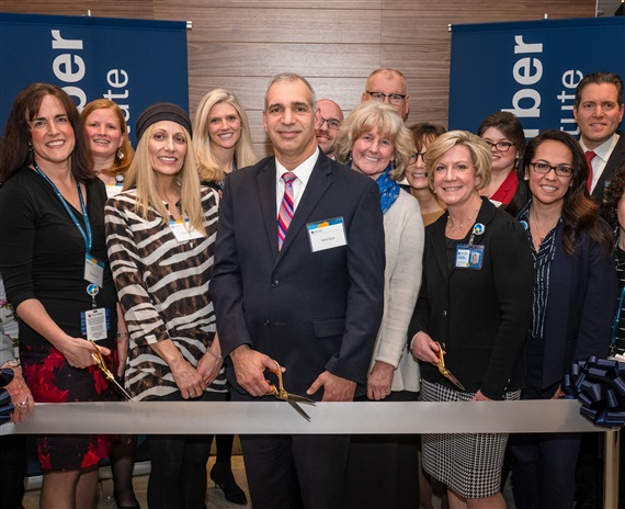 Yamil Kouri, MD, leads patients and staff in cutting the ribbon to open the new facility.